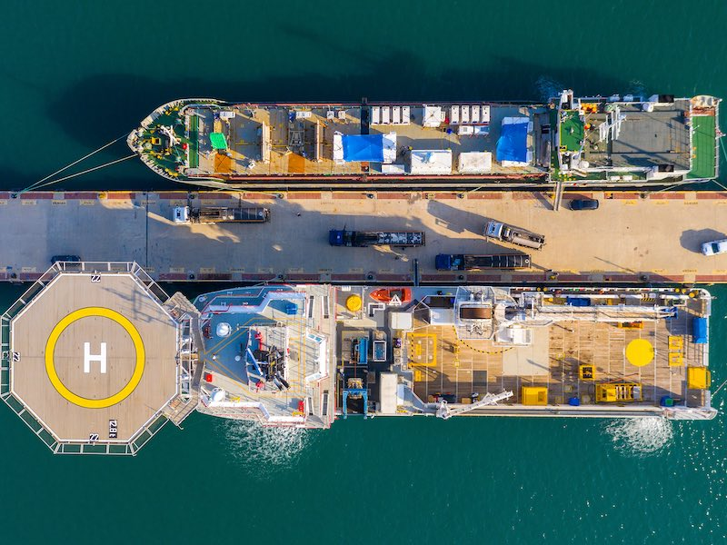 Offshore supply Ship docked next to a general Cargo vessel, Aerial image.